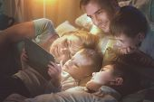 Happy family- Father, Mother and three kids lying down on the sofa and using tablet pc at night. Big poster