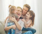 Happy mothers day! Two children daughters with father congratulate mom. Mum, dad and girls laughing poster