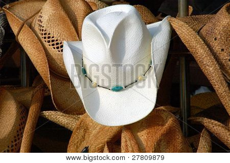 Full frame of cowboy hats. Central focus on the lone white hat in the middle