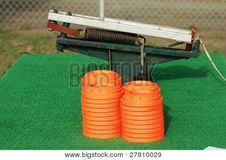 Clay pigeons stacked next to a portable trap thrower mounted on a table at a trap and skeet club