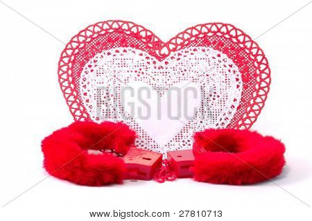 Valentine's Day image depicting the concept Caught in love. Lace doilie hearts and furry handcuffs