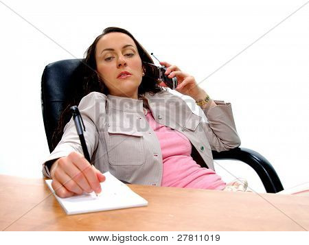 Serious business woman at her desk talking on cell phone and taking notes
