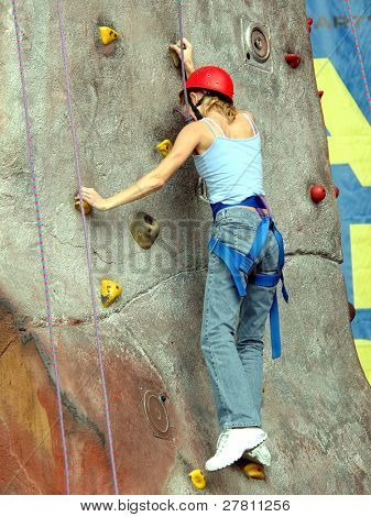 A young woman scaling an artificial rock climbing wall
