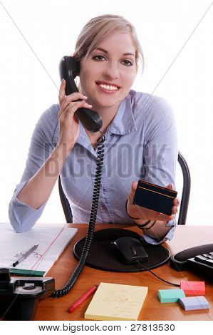 Credit card customer service representitive holding blank credit card toward the camera while talking on the phone.