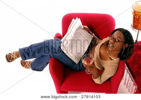 Beautiful African American woman in glasses and casual fashion reclined in a chair with a martini and the business pages of the newspaper.