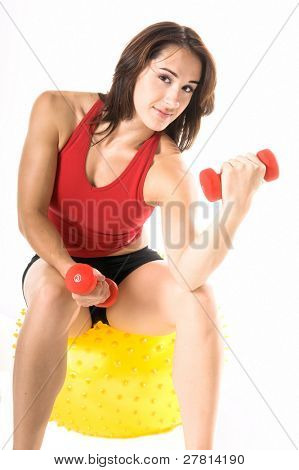 Fit and trim woman working out with dumbells while sitting on a Yoga ball
