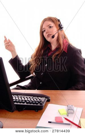 Female corporate executive in a power conversation on the headset phone in her office