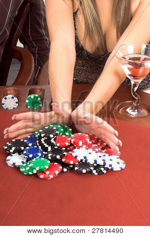 Detail of a womans hands placing an All In bet in a Texas Holdum Poker game