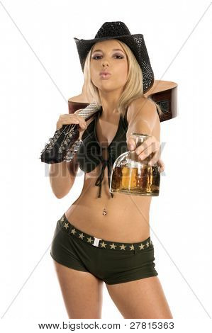 Beautiful blond woman in a bikini and cowboy hat with an acoustic guitar over her shoulder offering an open bottle of tequila.