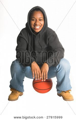 Sexy inner city African American woman in jeans and a sweat shirt playing basketball
