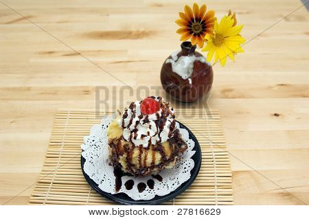 Assign dessert of deep fried Tempura Ice cream with whipped cream and chocolate sauce and topped with a maraschino cherrie