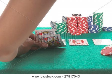 Texas Hold 'Um poker player peels back her cards to reveal a suited King and Jack of hearts that could potentially lead to a  hearts Royal Flush Generic no label card backs from China