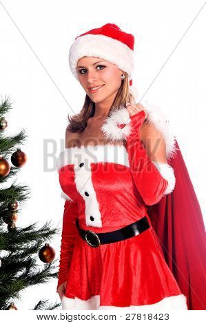 Sexy Ms. Santa Claus by the Christmas tree with a bag over her shoulder
