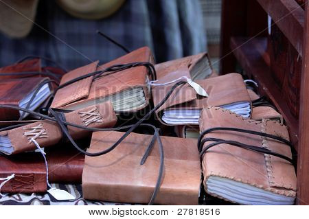 A pile of hand tooled leather bound journals on a library table