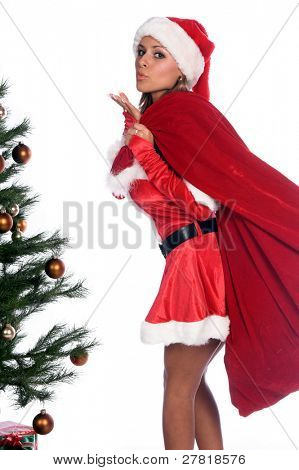 Sexy Ms. Santa Claus by the Christmas tree with a bag of gifts over her shoulder and blowing a kiss