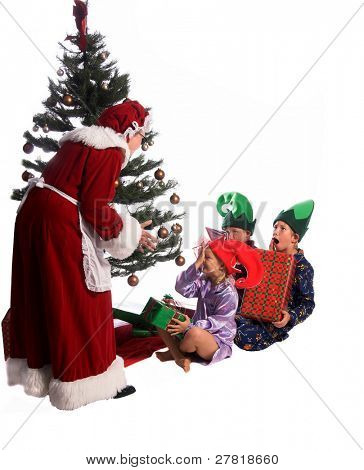 A group of children sitting under the Christmas Tree as Mrs. Santa Claus arrives and begins to hand out the gifts.