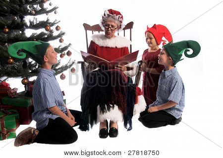 A group of children gathered around Mrs. Santa Claus sitting in her rocking chair and reading them a story.