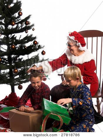 Two young boys excitedly gathered around the Christmas Tree opening their gifts while Mrs. Santa Claus sits watching from  her rocking chair.