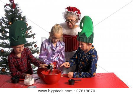 A group of young children aged 6 - 12 wearing elf hats and pj's baking cookies with Mrs. Santa Claus. One boy pointing at the bowl, one boy adding flour and the girl stirring while Mrs Claus looks on