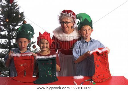 A group of young children aged 6 - 12 wearing elf hats and working with Mrs. Santa Claus show off the end result of their Christmas craft project of decorating  stockings