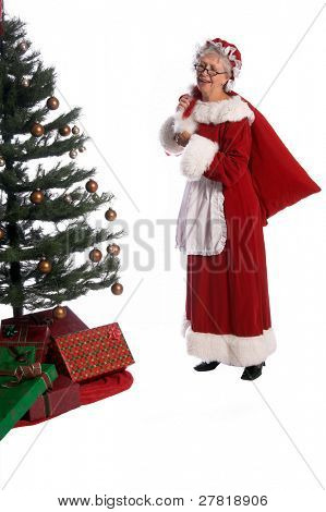 Mrs Santa Claus in a fur trimmed red velvet dress and bonnet with a bag of toys over her shoulder delivering Christmas presents under the tree