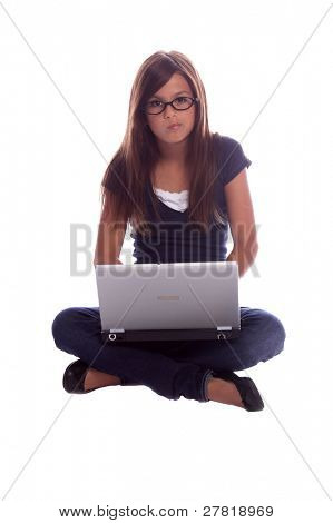 Young girl sitting cross legged and thinking with a laptop computer on her lap