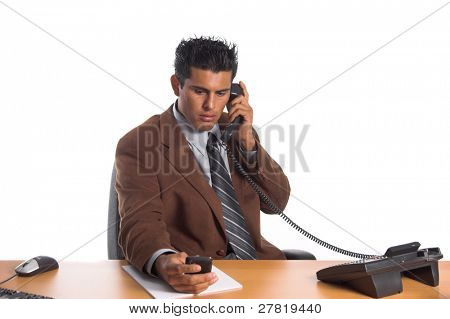 Handsome young Hispanic business man multitasking at his desk. Taking a phone call and sending email on his cell phone