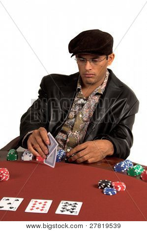 Gambler looking at his hole cards while playing Texas Hold um poker.