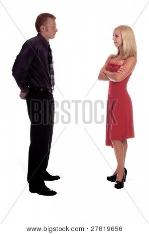 Young adult man facing upset woman with crossed arms who thinks he has forgotten Valentine's Day