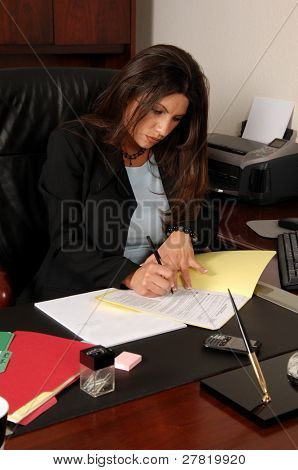 Female executive intently signing her tax forms while sitting at her desk