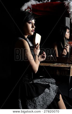 Beautiful raven haired Gothic Vampire Slayer in a black and grey dress brushing her hair while sitting at her vanity.