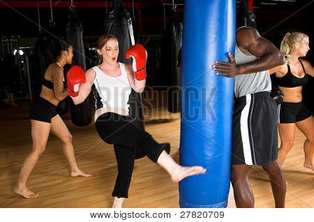 Woman kicking a heavy bag during a kick boxing class in an MMA gym
