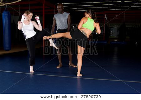 Young female MMA fighters working on body kicks with their personal trainer in the gym