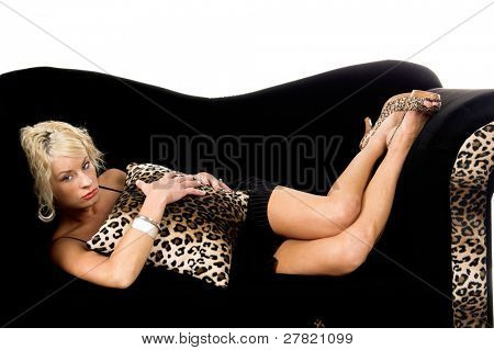 Pretty blonde fashion model with short blond hair laying on a black and leopard print couch looking very sad and depressed