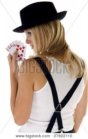 Over the shoulder view of a young blonde woman in a fedora holding a hearts Royal Flush in her hand