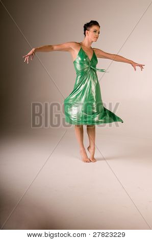 Female dancer in a metallic green dress performing a spin