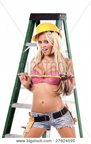High fashion glamour model in Daisy duke shorts, tool belt, pink bra and yellow hard hat on a ladder with a measuring tape