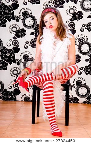 Beautiful young woman wearing red and white striped tights and high heels and a white feather boa
