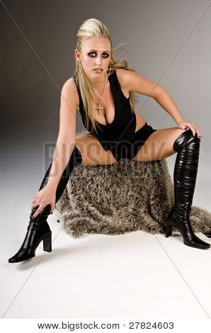 Pretty blonde in pinstripe and lace vest, booty shorts, thigh high boots  with dark and edgy eye makeup sitting on a fuzzy seat