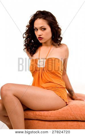 Beautiful multi ethnic woman of Spanish and Native American descent wearing an orange dress and sitting on an upholstered hassock