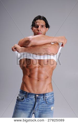 Muscular young man standing in jeans and taking off a white wife beater tee shirt