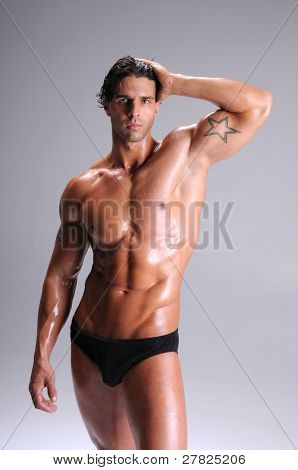 Muscular young man standing bare chested in black brief style underwear