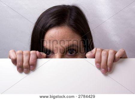 Female Peering Over Blank White Sign