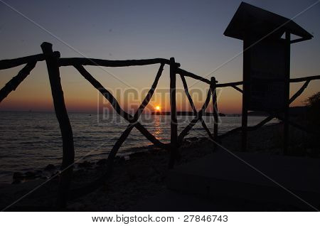 Sunset in Menorca looking through stair rails along the seafront