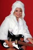 Sexy blond snow bunny in a white furry coat and hat and black hot pants over a red background with an electric guitar poster