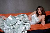 stock photo of futon  - Pretty young Mexican woman laying on a couch in a formal satin gown - JPG