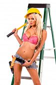 High fashion glamour model in Daisy duke shorts, tool belt, pink bra and yellow hard hat on a ladder