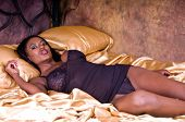 Sexy African American woman with very large breasts looking lovely in black lingerie  in a gold bedr