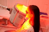 Red Light Therapy. The Girl Goes Through A Course Of Skin Rejuvenation With The Help Of Red Light Tr poster