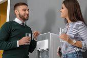 Employees Having Break Near Water Cooler In Office poster